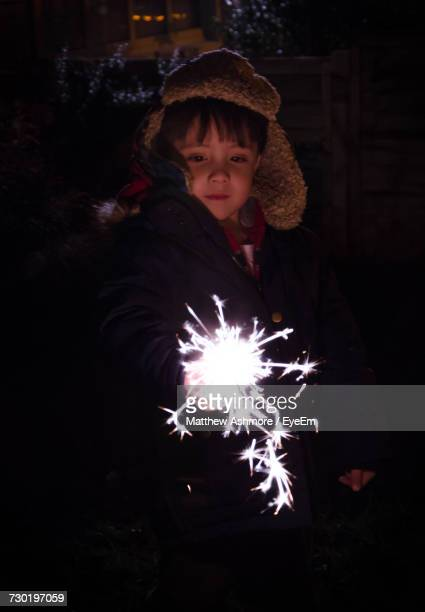 Boy Holding Burning Sparkler While Standing At Night