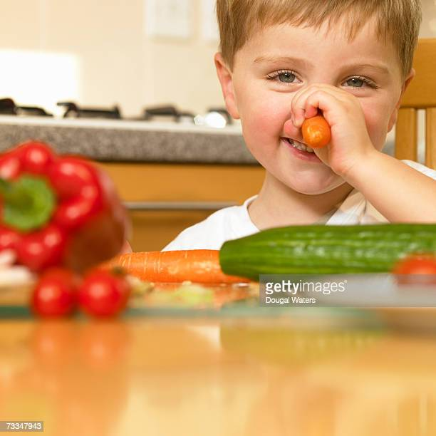 Boy (3-5) holding carrot up to nose, smiling, portrait