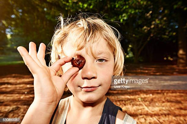 Boy holding chestnut, portrait, close up