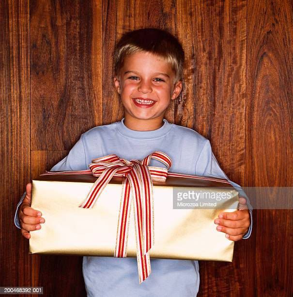 boy (3-5) holding christmas present, smiling, portrait - microzoa stock pictures, royalty-free photos & images