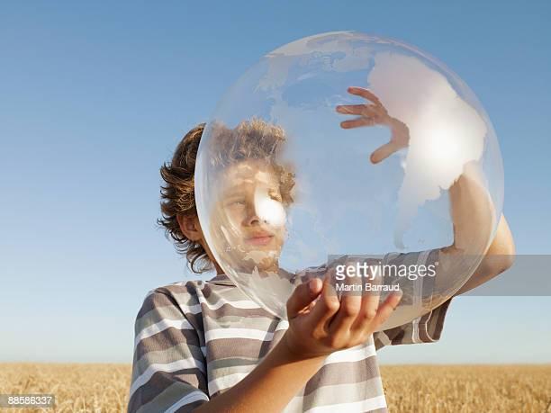 Boy holding clear globe in field