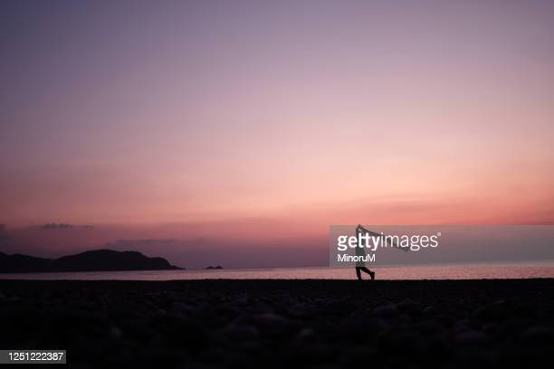 boy holding cloth walking along the beach - hope stock pictures, royalty-free photos & images