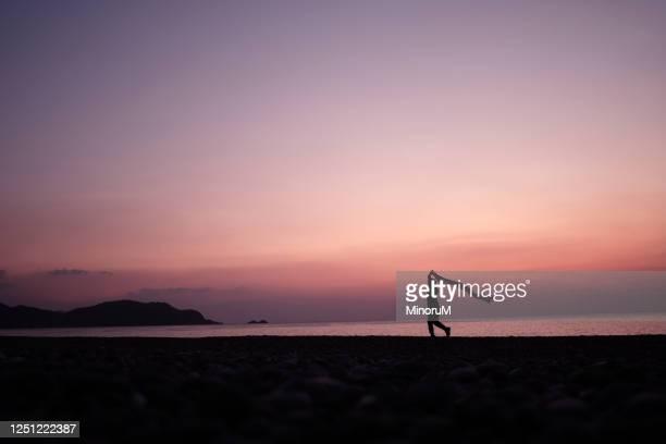 boy holding cloth walking along the beach - 自然 ストックフォトと画像