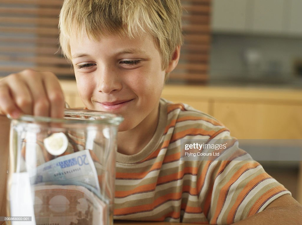 Boy (7-9) holding coin in money jar, smiling, close-up : Stock Photo