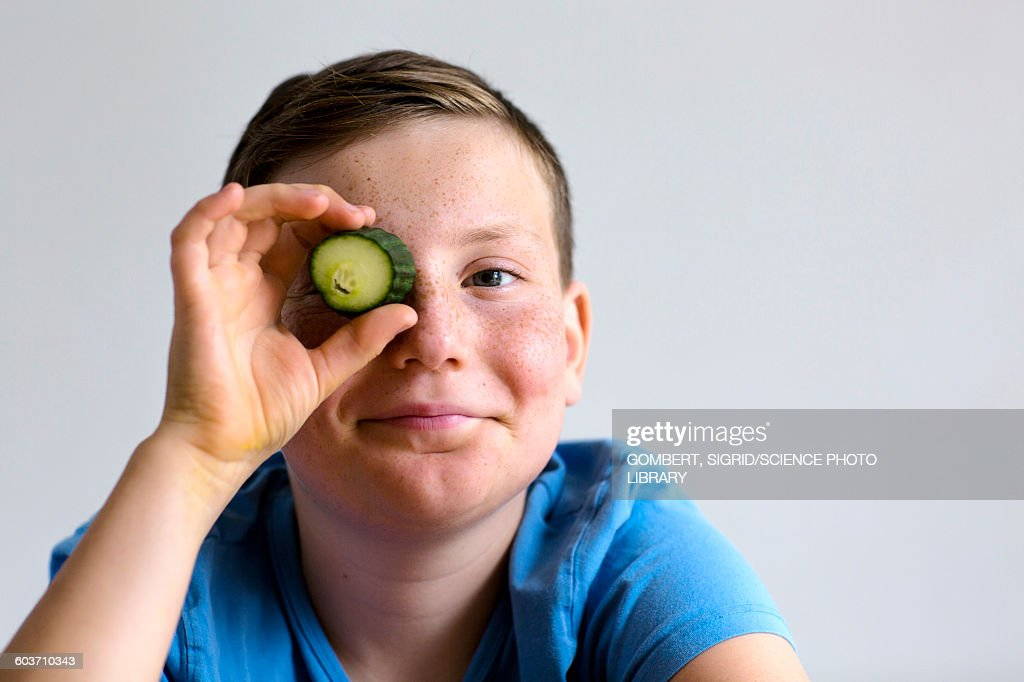 Boy holding cucumber over eye : Stock-Foto