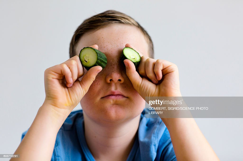 Boy holding cucumber over eyes : ストックフォト