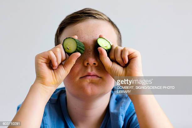 boy holding cucumber over eyes - sigrid gombert stock pictures, royalty-free photos & images