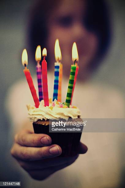 boy holding cupcake with birthday candles - catherine macbride stockfoto's en -beelden