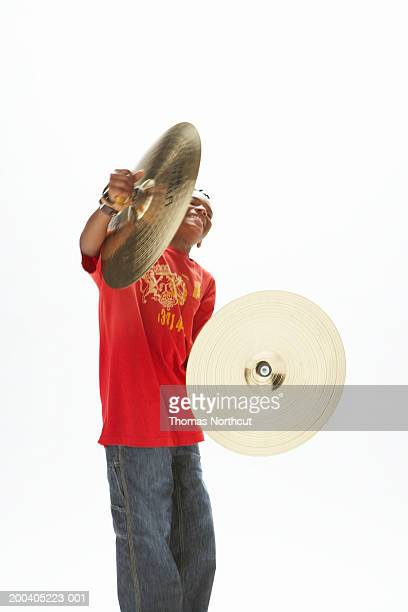Boy (9-11) holding cymbals, eyes closed (blurred motion)