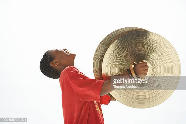 boy (9-11) holding cymbals, head back, eyes closed, side view - platillo fotografías e imágenes de stock