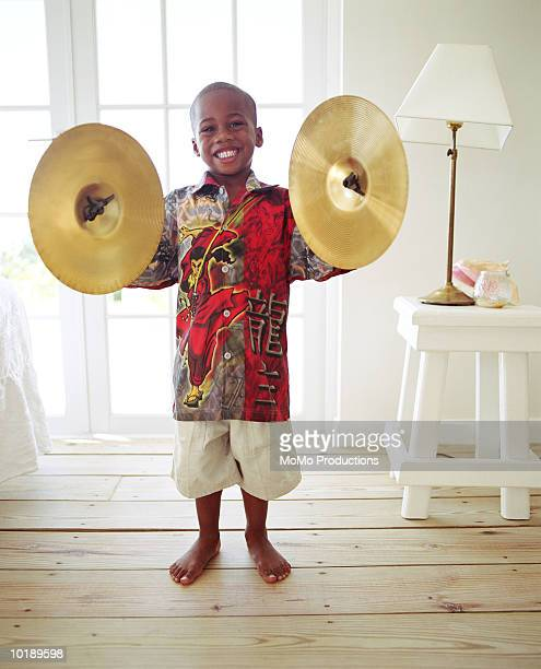 Boy (6-8 years) holding cymbals in living room