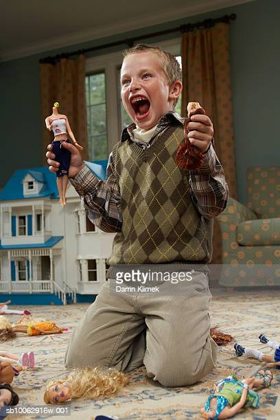 boy (6-7 years) holding decapitated dolls and yelling - vernieling stockfoto's en -beelden