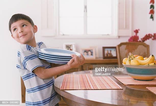 Boy Holding Dinner Plates