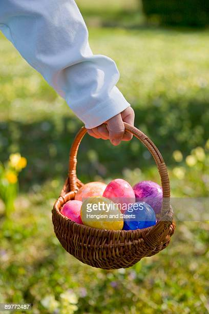 boy holding easter basket, painted eggs - chasse aux oeufs de paques photos et images de collection