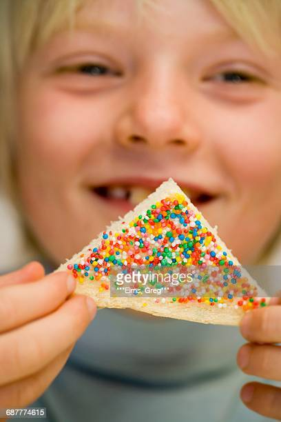 Boy holding fairy bread (Bread triangle with sprinkles, Australia)