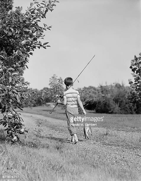 boy holding fish and fishing rod walking away - {{relatedsearchurl(carousel.phrase)}} stock pictures, royalty-free photos & images