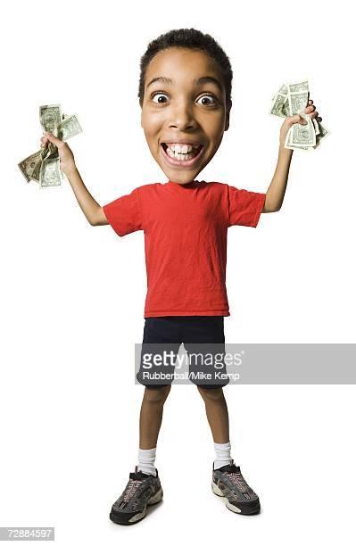 Boy holding fistfuls of US dollar bills