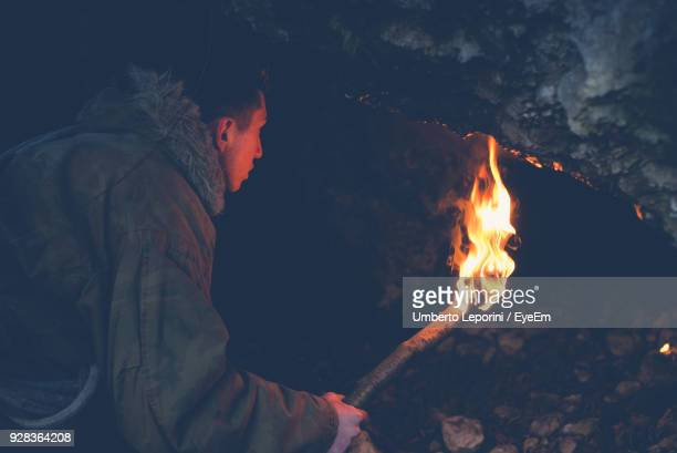 boy holding flaming torch in cave - cave fire stock photos and pictures