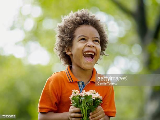 boy (3-5) holding flower, laughing - nur jungen stock-fotos und bilder