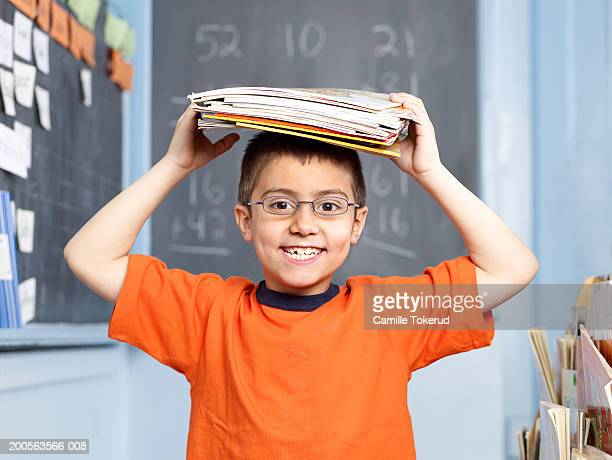 Boy (8-9) holding folders on head, portrait