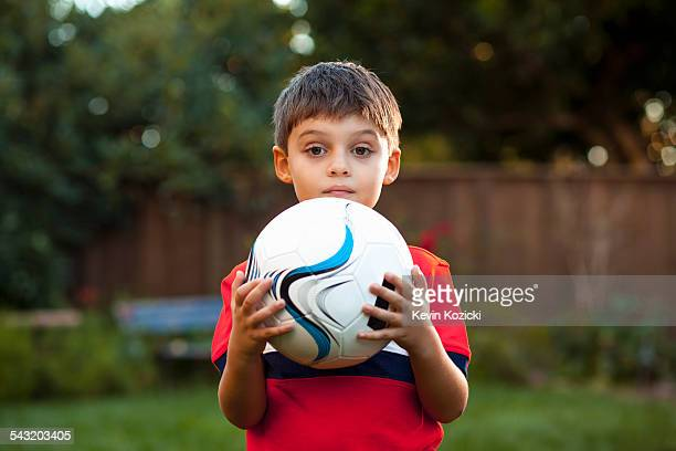 Boy holding football against chest in garden
