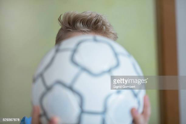 boy holding football in front of his face, freiburg im breisgau, baden-w��rttemberg, germany - sigrid gombert stockfoto's en -beelden