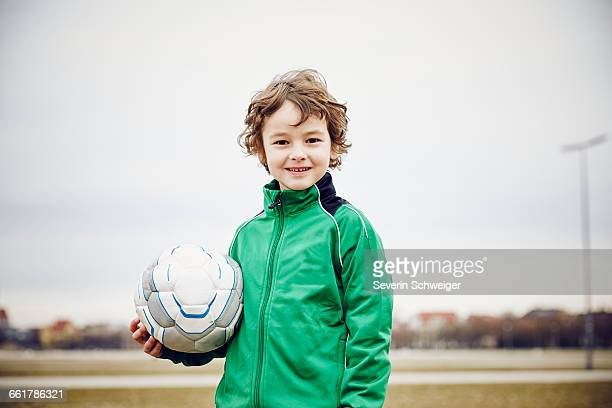 Boy holding football looking at camera smiling