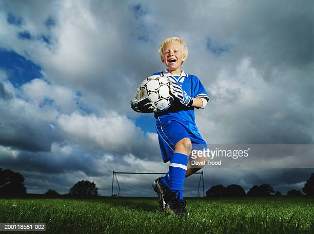 Boy (6-8) holding football on playing field, portrait, low angle view