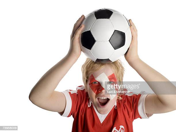 Boy (10-13) with Austrian flag painted on face, holding football above head, portrait