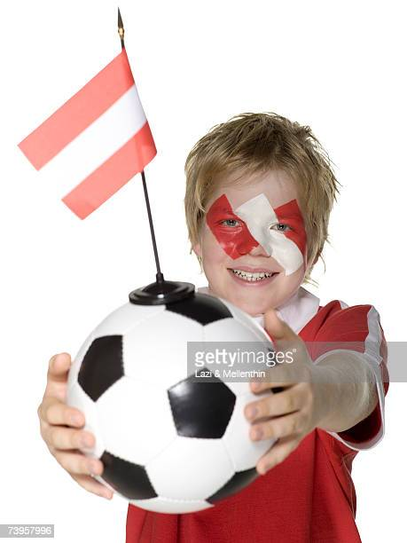 Boy (10-12) holding football, Austrian flag painted on face, smiling