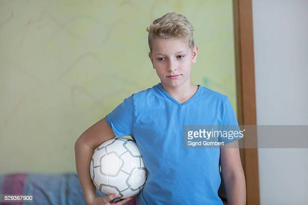 boy holding football under his arm and looking down, freiburg im breisgau, baden-w��rttemberg, germany - sigrid gombert stock pictures, royalty-free photos & images