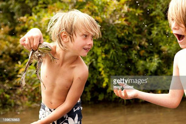 Boy holding frog up whilst friend looks on in amazement