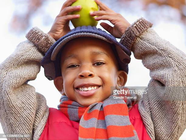 Boy (4-5) holding fruit on head, smiling, portrait