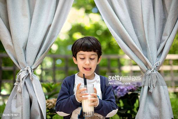 Boy holding glass of milk looking down