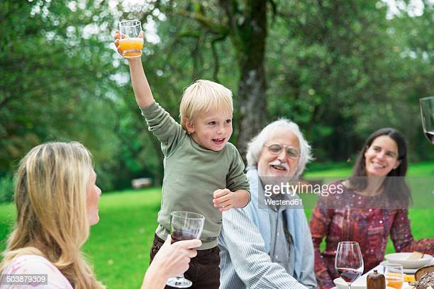 Boy holding glass on a garden party