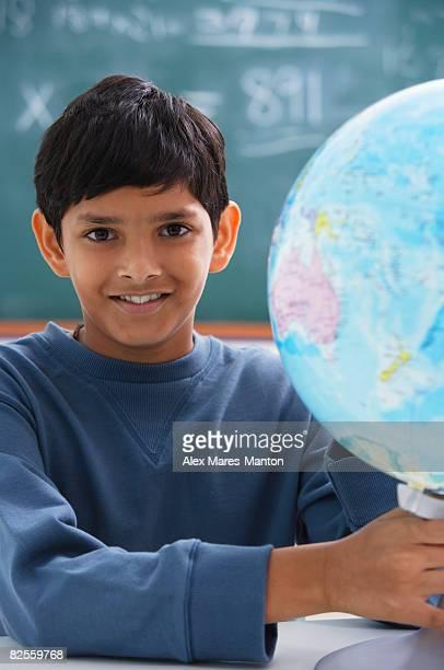 boy holding globe, gray sweatshirt