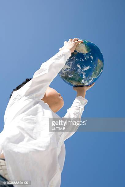 Boy (12-13) holding globe, low angle view against blue sky
