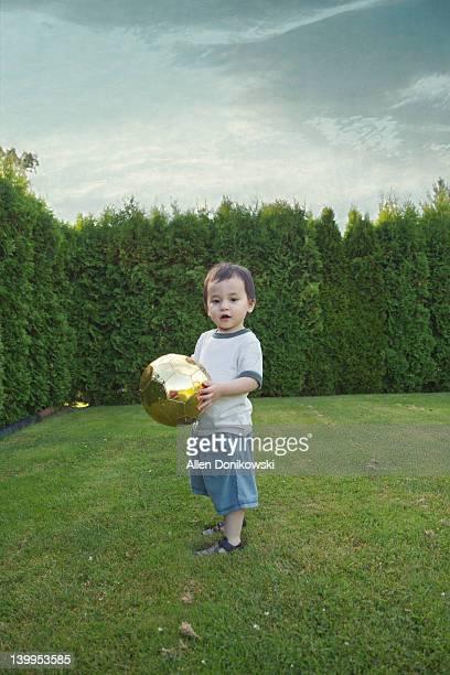 Boy holding gold soccer ball