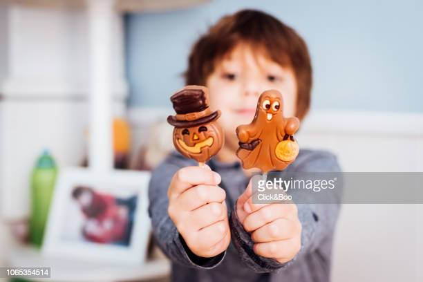 Boy holding Halloween sweets in front of the camera