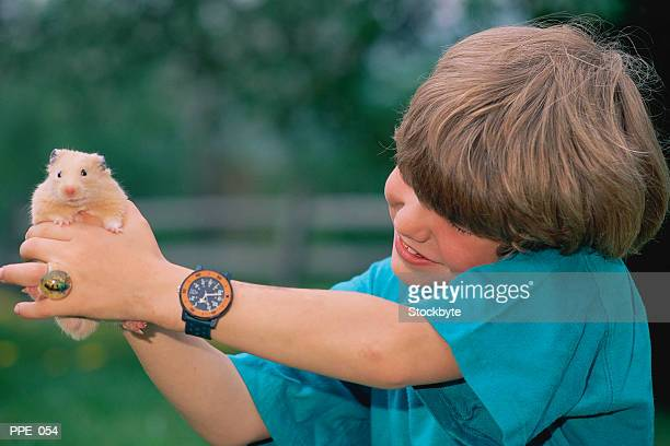 Boy holding hamster at arm's length