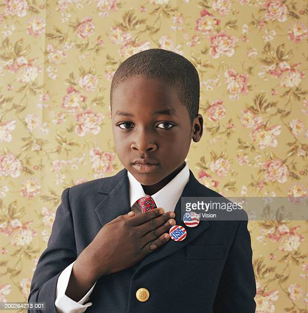 boy (9-11) holding hand to chest, portrait - president stockfoto's en -beelden