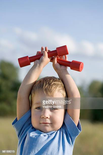A boy holding hand weights above his head