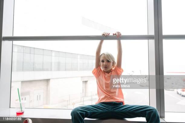 boy holding handrail in airport window seat, three quarter length portrait - three quarter length ストックフォトと画像