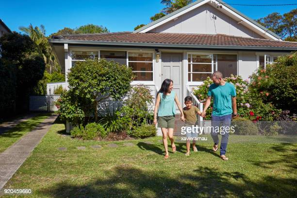 Boy holding hands of parents while walking in lawn