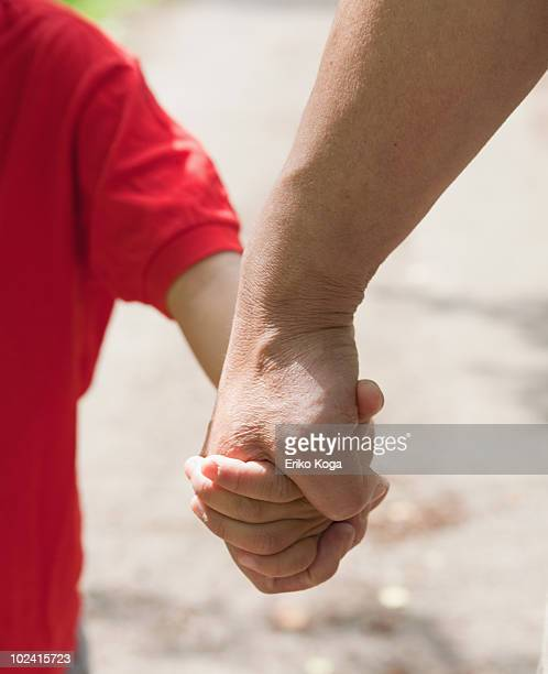 Boy holding hands with grandfather