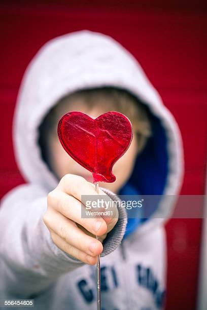 Boy holding heart-shaped lollipop