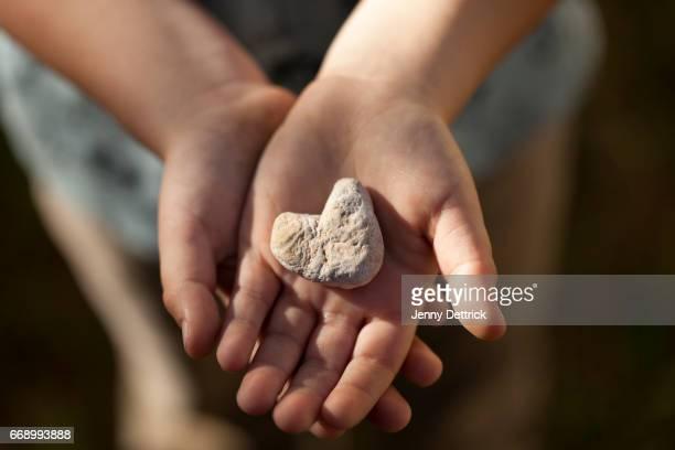 Boy holding heart-shaped stone