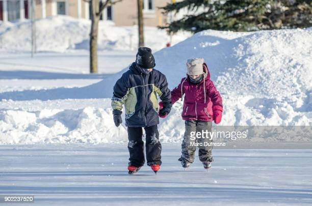 Boy holding her sister's hand to help her ice skating