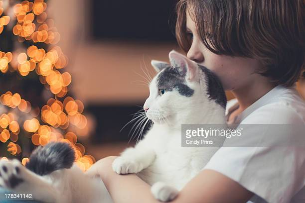 A boy holding his cat during Christmas