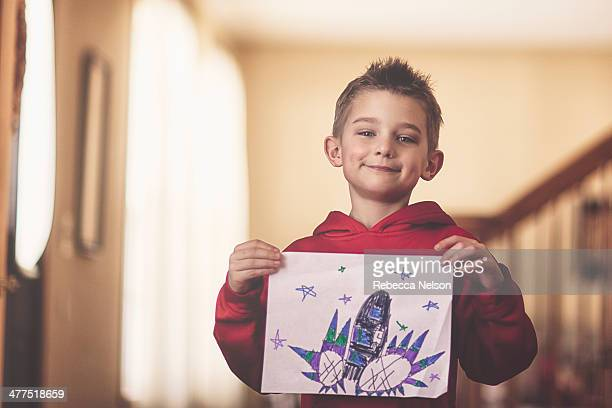 boy holding his drawing of a rocket
